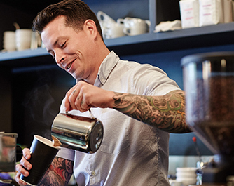 Tattooed barista making coffee